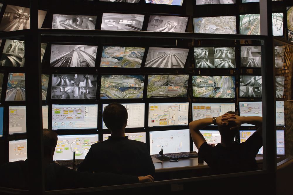 security guards looking at monitoring station video screens