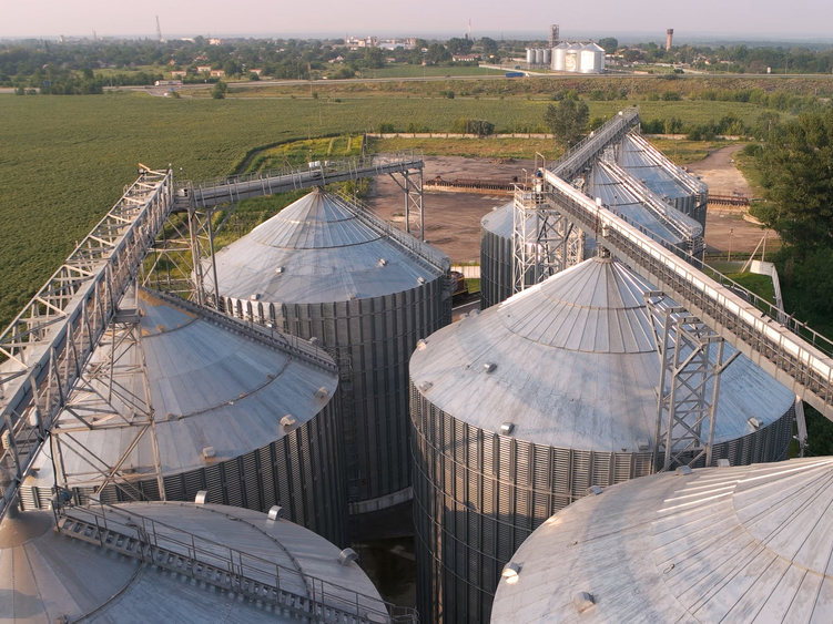 video surveillance security cameras on top of agriculture grain silos in farm field
