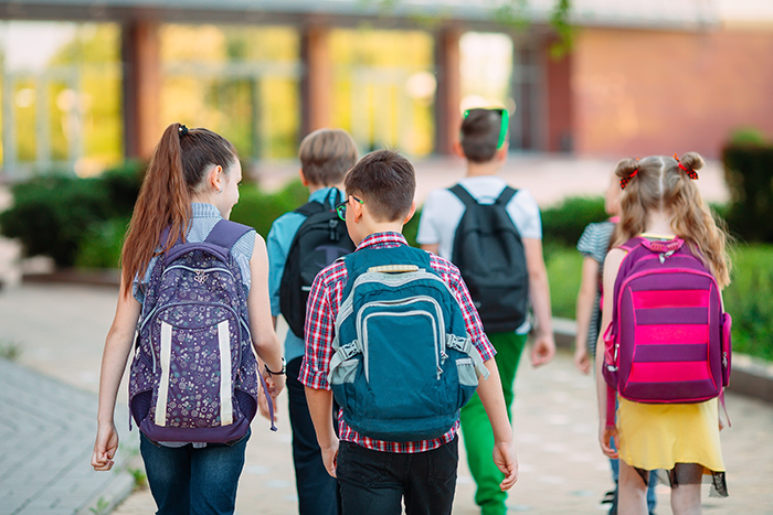 young students with backpacks walking to school