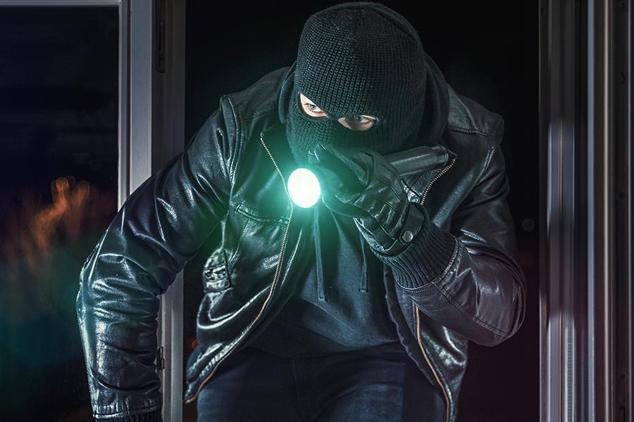 burglar with flashlight breaking into business alarm