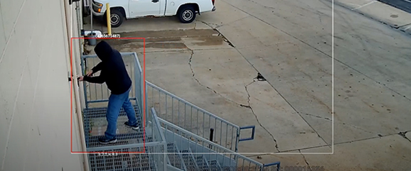 man breaking into business, watched by security video surveillance cameras