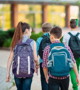 elementary students walking to school with backpacks