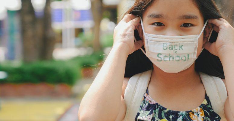 grade school student wearing COVID mask at school